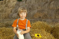 Criança no monte de feno com pão e leite Imagem de Stock