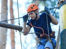 Criança no parque da aventura da floresta A criança no capacete alaranjado e na camisa azul de t escala na fuga alta da corda fotografia de stock royalty free