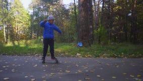 Criança no passeio do menino do skate no patim exterior no parque do outono