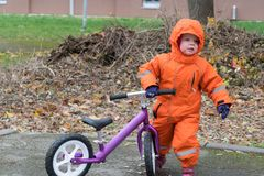 Criança no roupa e capa mornas com bicicleta do equilíbrio imagens de stock royalty free