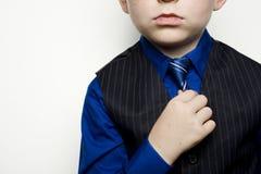 Criança no terno de negócio que ajusta o laço Imagens de Stock