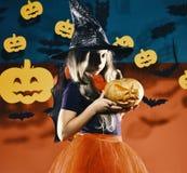 A criança no traje da princesa da bruxa guarda a lanterna do jaque o Chapéu negro vestindo da bruxa pequena Conceito do partido d Fotografia de Stock Royalty Free