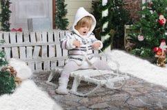 Criança no trenó na jarda da neve do inverno Imagem de Stock