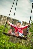 Criança nos balanços imagem de stock royalty free