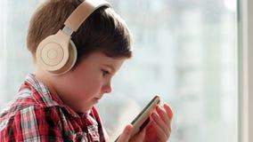 Criança nos fones de ouvido que sorri, desenhos animados de observação no dispositivo eletrônico, dispositivos do rapaz pequeno p video estoque