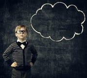 A criança nos vidros pensa a bolha sobre o quadro-negro, pensamento do menino da criança foto de stock