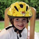 Criança nova com o capacete da bicicleta no amarelo Imagem de Stock Royalty Free