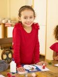 Criança nova da raça misturada que faz cartões de Natal Imagens de Stock Royalty Free