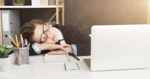 A criança nova do homem de negócios no terno de negócio fica cansado e caiu adormecido fotografia de stock royalty free