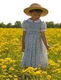 Criança nova no campo de flores amarelas Fotografia de Stock