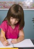 Criança nova que trabalha em sua mesa no quarto de classe fotos de stock royalty free