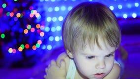 A criança olha à tabuleta que encontra-se na cama No fundo, nas luzes e nas festões do abeto do Natal filme