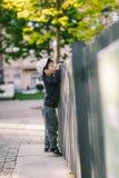 A criança olha através do furo na cerca fotografia de stock
