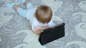 A criança olha desenhos animados no PC da tabuleta no assoalho filme