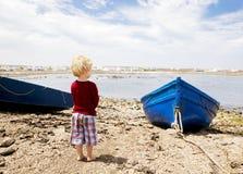 A criança olha fixamente para fora sobre uma baía com barcos de pesca foto de stock royalty free