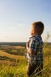A criança olha na distância Fotos de Stock Royalty Free