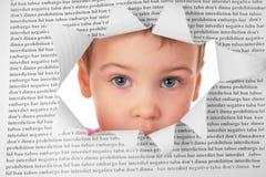 A criança olha no furo na folha de papel fotos de stock