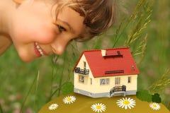 A criança olha no modelo da casa ao ar livre Foto de Stock Royalty Free