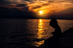 A criança olha no smartphone no fundo de um por do sol bonito foto de stock