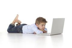 A criança olha o portátil Imagens de Stock Royalty Free