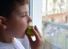 A criança olha para fora a janela e morde a maçã verde Um menino guarda uma maçã em sua mão foto de stock royalty free