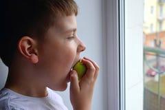 A criança olha para fora a janela e morde a maçã verde Um menino guarda uma maçã em sua mão fotos de stock royalty free
