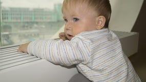 A criança olha para fora a janela na cidade fotografia de stock royalty free