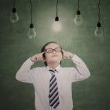 Criança pensativa do negócio sob bulbos iluminados Imagem de Stock Royalty Free
