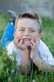 Criança pensativa que encontra-se na grama Fotos de Stock Royalty Free