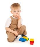 Criança pensativa que joga com os brinquedos isolados Foto de Stock Royalty Free
