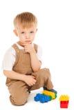 Criança pensativa que joga com os brinquedos isolados Fotos de Stock Royalty Free