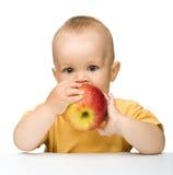 A criança pequena é maçã vermelha cortante Fotos de Stock