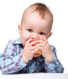 A criança pequena é maçã vermelha cortante e sorriso Fotografia de Stock Royalty Free