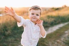 criança pequena adorável que sorri na câmera ao andar fora imagem de stock royalty free