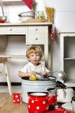 A criança pequena adorável senta-se na cozinha dentro de uma bandeja Fotografia de Stock Royalty Free