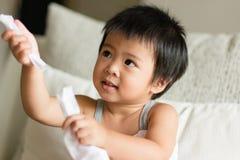 A criança pequena asiática entrega puxar e compartilhar do lenço de papel branco fotos de stock