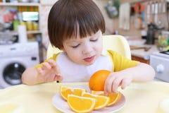 Criança pequena bonita que come a laranja Fotos de Stock
