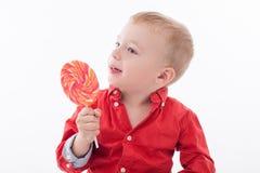 A criança pequena bonito está apreciando doces doces imagem de stock