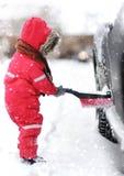 Criança pequena bonito que ajuda a escovar uma neve de um carro imagens de stock royalty free