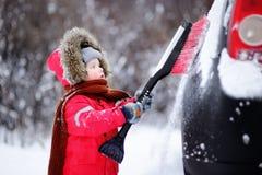 Criança pequena bonito que ajuda a escovar uma neve de um carro foto de stock