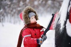 Criança pequena bonito que ajuda a escovar uma neve de um carro imagem de stock royalty free