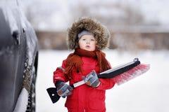 Criança pequena bonito que ajuda a escovar uma neve de um carro fotografia de stock royalty free