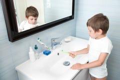Criança pequena bonito que lava sua escova de dentes sob o córrego da água no banheiro foto de stock royalty free