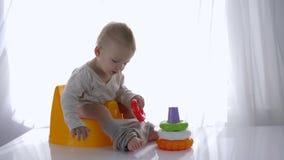 A criança pequena bonito senta-se no urinol e no jogo com a pirâmide plástica educacional dos brinquedos na sala brilhante vídeos de arquivo