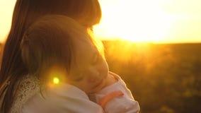 A criança pequena caiu adormecido nos braços de suas mãe, mamã da caminhada e filha no por do sol no parque no verão, lento-movim