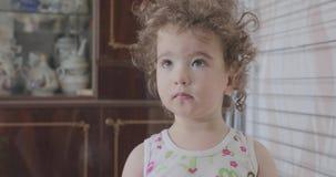 A criança pequena com cabelo encaracolado está olhando acima e sua cara está refletindo emoções diferentes video estoque