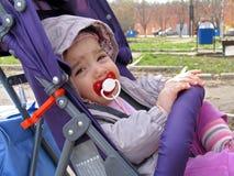 Criança pequena com a chupeta que senta-se na cadeira de rodas Fotografia de Stock Royalty Free