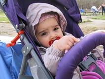 Criança pequena com a chupeta que senta-se na cadeira de rodas Fotos de Stock