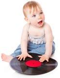 A criança pequena com um registro de gramofone preto Imagem de Stock Royalty Free