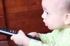 Criança pequena com uma tevê de controle remoto Foto de Stock